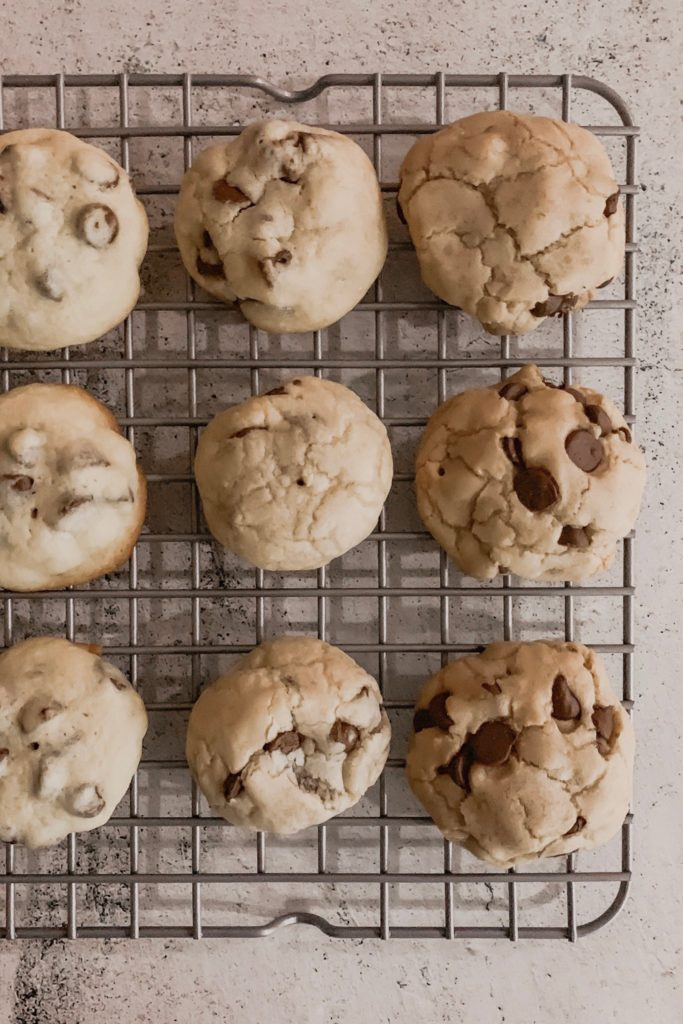 Chocolate chip cookies cooling on a baking rack.