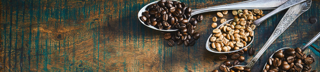 Coffee beans in spoons on a nice wooden table.