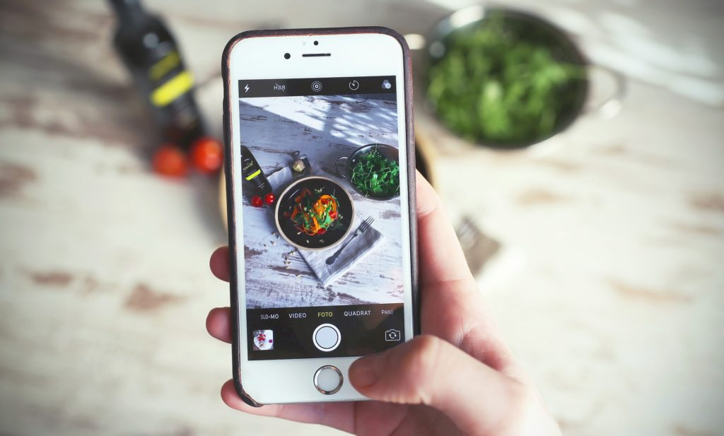 Person taking picture of food on an iphone
