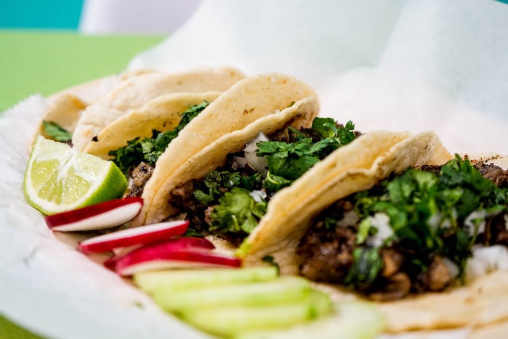 Delicious tacos prepared on a plate with fresh vegetables.