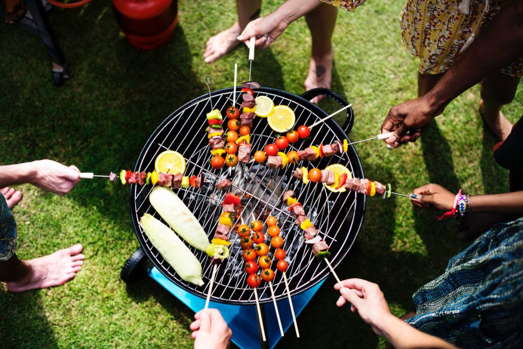 People gathered around a grill with kebabs or skewers