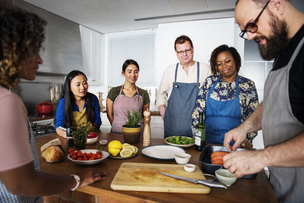 People gathered around a chef during a cooking demo with a chef.
