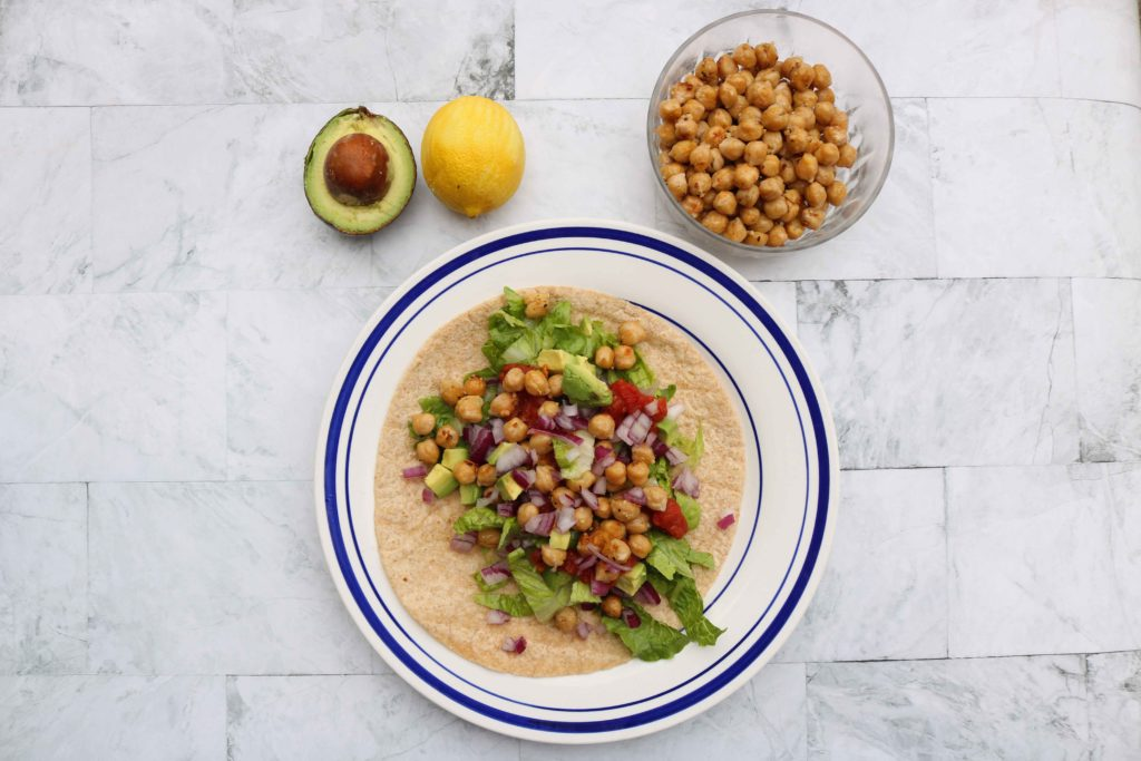 Chick pea recipe and tortillas on a plate with side of avocado and lemon.
