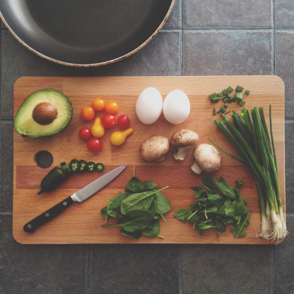 Fresh vegetables on a cutting board, such as spinach and peppers