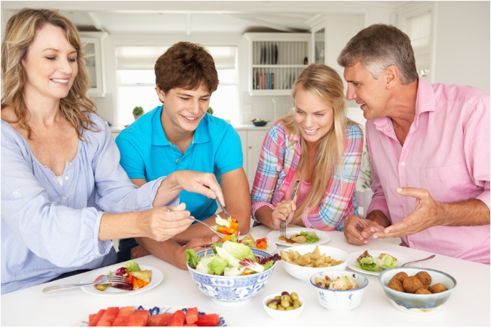 Family sitting at table eating together